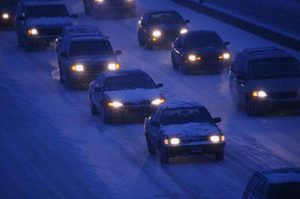 Cars on a snow covered roadway in dangerous driving conditions